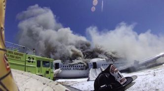 Flight 214 burning as firefighters scramble to control the fire in the cabin.