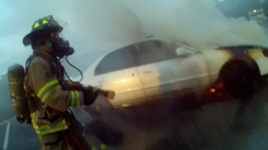 Firefighter advancing on car fire.